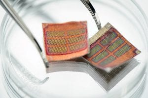 Woven solar textiles are seen next to a pair of tweezers in a photo at the University of Wisconsin-Madison on Sept. 30, 2015. Coated in conductive polymer material, each half-inch square of fabric contains an array of six rectangular solar cells. The technology is a result of research collaboration between Trisha Andrew, assistant professor of chemistry, and Marianne Fairbanks, assistant professor in the School of Human Ecology's design studies program. (Photo by Jeff Miller/UW-Madison)