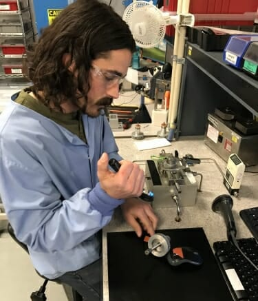 Tyler Vermey, a UW–Madison engineering alum, works on flow control valves at GE Healthcare's Madison plant. PHOTO COURTESY OF GE HEALTHCARE