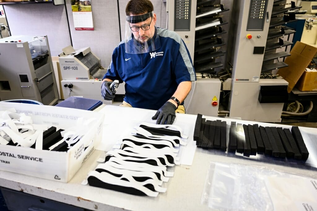 Staff member Ken Parman fabricates and packages custom-made medical face shields at the Division of Information Technology's Digital Publishing and Printing Services facility. Photo by Jeff Miller