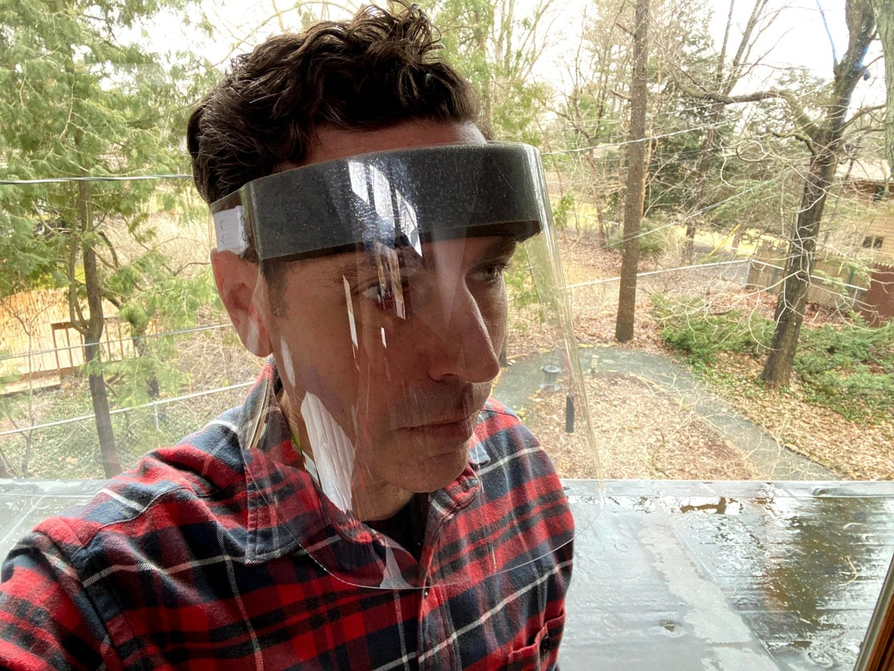 Jesse Darley, an engineer who worked on the face shield's open source design, models a prototype at his home. PHOTOGRAPH: JESSE DARLEY