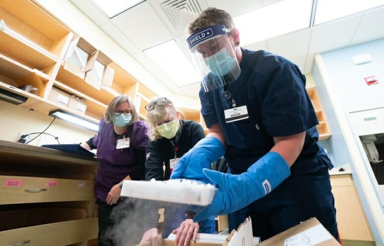 UW Health pharmacy technicians, from left, Amy Schultz, Susan Johnston and Nikolas Gardner unpack a box of Pfizer's COVID-19 vaccine soon after its arrival. PHOTO BY JOHN MANIACI, UW HEALTH