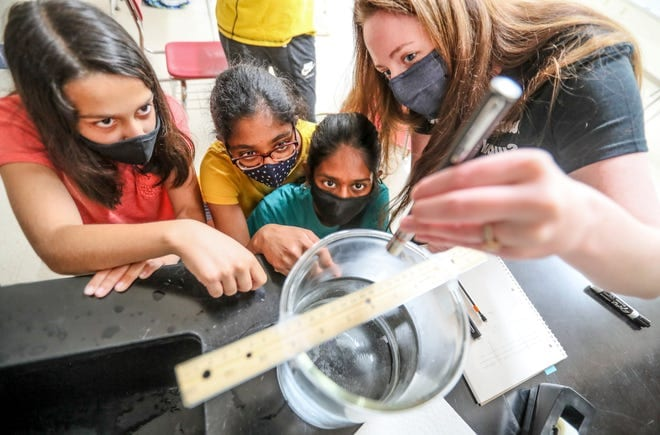 From left to right, Raghvi Sethi, 13, Radhika Gupta, 12, and Rishika Kommuri, 13, watch as Mallory Conlon, UW-Madison Department of Physics Quantum Science Outreach Program coordinator, shines a laser to see if different colored laser lights impact the light refraction in water. The students were participating in the Wisconsin Heights Summer Science Camp outside Madison. Photo: Ebony Cox / Milwaukee Journal Sentinel