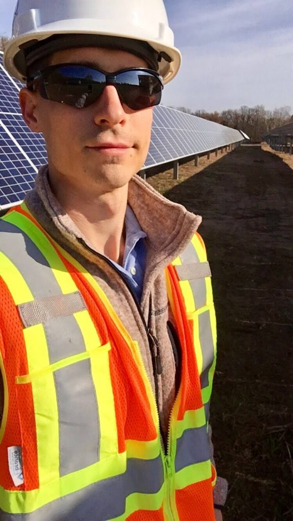 Josh Cook stands in front of a solar installation. Photo courtesy of EDF Renewables.